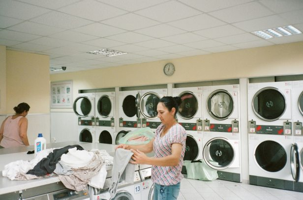 photo-of-woman-standing-inside-the-laundromat-2927523